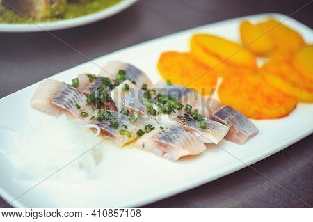 Delicious Pieces Of Icelandic Herring With Onions On A White Plate. Raw Salted Herring On Wooden Bac