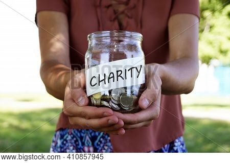 Charity. Glass Jar With Coins And Inscription Charity In The Hands Of The Girl. The Concept Of Colle