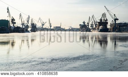 Cranes Of Of The Baltic Shipyard On A Frosty Winter Day, Steam Over The Neva River, Smooth Surface O