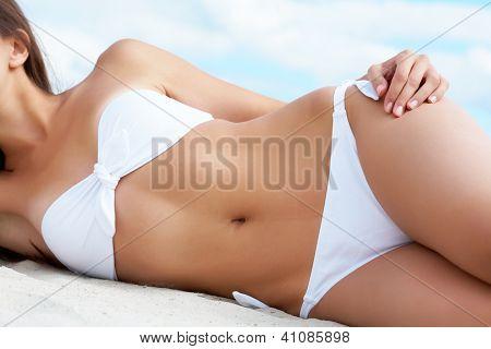 Torso of luxurious woman in white bikini sunbathing