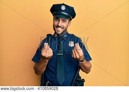 Handsome hispanic man wearing police uniform doing money gesture with hands, asking for salary payment, millionaire business