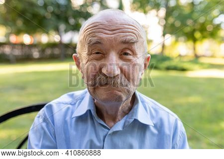 Portrait Of Senior Man With White Mustache Looking At Camera And Making Faces. Man Looking Goofy And