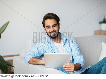 Portrait Of Young Smiling Arab Man With Digital Tablet Relaxing At Home, Millennial Eastern Guy Sitt