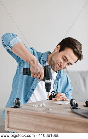 Electric Drill Works In Handyman Hands, Assemble And Repair Furniture At Home. Concentrated Millenni