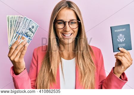 Young blonde woman wearing business style holding dollars and usa passport smiling and laughing hard out loud because funny crazy joke.