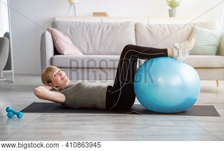 Fit Mature Lady Doing Abs Exercises On Yoga Mat At Home, Training Her Core Muscles With Fitball, Cop