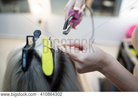Hairdresser Female Making Hair Extensions To Young Woman With Blonde Hair In Beauty Salon. Professio