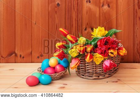 Easter Concept. Colorful Tulips  And Easter Eggs In Wicker Baskets On Wooden Table. Selective Focus.