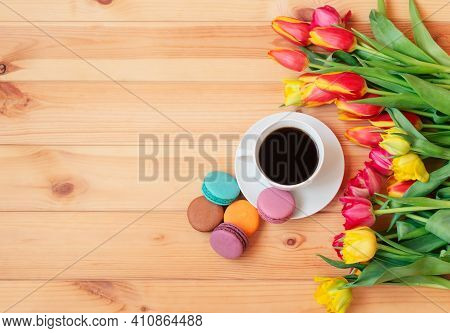 Colorful Tulips And Cup Of Coffee With Colorful Macaroons As Border On Wooden Table. Top View, Copy