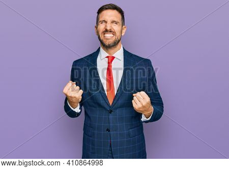 Handsome man with beard wearing business suit and tie very happy and excited doing winner gesture with arms raised, smiling and screaming for success. celebration concept.