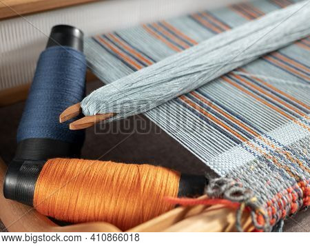 Handloom With Shuttle On The Blue Warp Threads And Two Bobbins With Indigo And Orange Yarns. Vertica