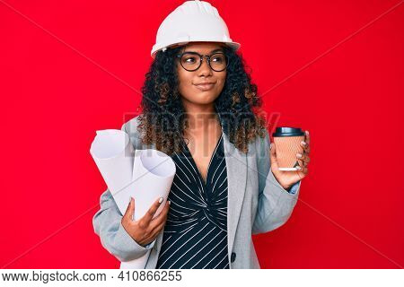 Young african american woman wearing architect hardhat holding blueprints and take away coffee smiling looking to the side and staring away thinking.