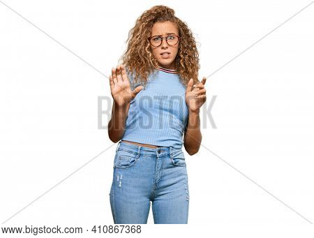 Beautiful caucasian teenager girl wearing casual clothes and glasses disgusted expression, displeased and fearful doing disgust face because aversion reaction. with hands raised