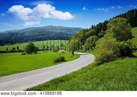 Beautiful summer mountain road and cloudy sky