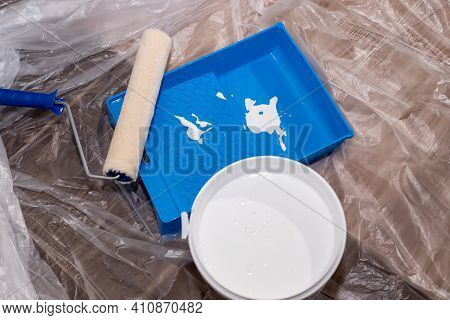 Tools For Priming Plastered Surfaces For Further Painting.paint Roller In A Blue Tray With White Pai