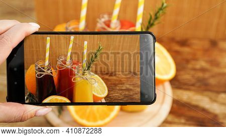 Woman Taking Picture Of Fruit Juice On Her Smartphone. Hand Holds A Phone With A Photo. Fruit Juices