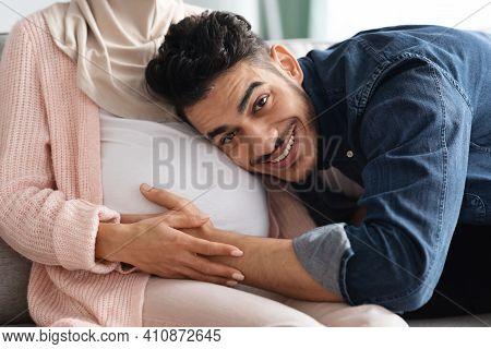 Future Father. Happy Arab Man Listening His Pregnant Wifes Belly, Loving Muslim Guy Embracing Big Tu