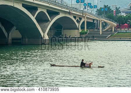 Guilin, China - May 11, 2010: Flat Raft With Fisherman On Green Water Li River Under Modern Lifang B