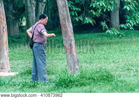 Guilin, China - May 11, 2010: Seven Star Park Landscape. Man Punishes A Tree With His Fists In A Tai