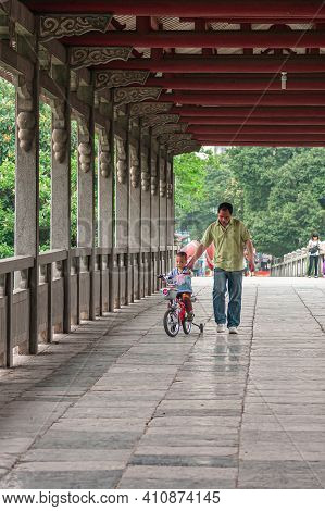 Guilin, China - May 11, 2010: Seven Star Park. Father Helps Son Riding Little Bike With Training Whe