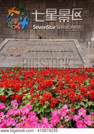Guilin, China - May 11, 2010: Seven Star Park Sign, Text, And Logo At Entrance Behind Red And Pink F