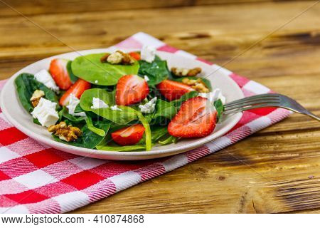 Fresh Healthy Salad With Strawberry, Spinach, Walnuts And Feta Cheese On Wooden Table