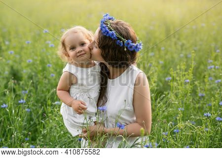Mother And Daughter In A Field Of Cornflowers At Sunset. A Wreath Of Cornflowers On The Head Of A Wo