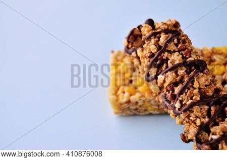 A Bar Of Muesli With Chocolate Lies On Another Muesli Bar On A Blue Background Close-up View From Th