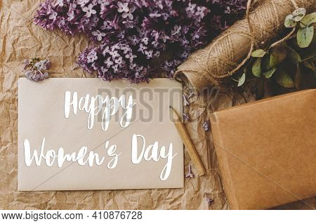 Happy Womens Day Text On Card And Lilac Flowers, Gift, Pencil And Twine On Rustic Background, Top Vi