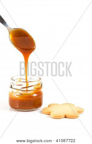 Pouring Caramel In A Small Jar With A Spoon With A Cookie Next To It, Vertical Shot
