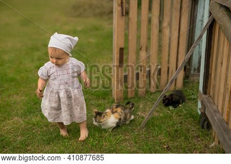 A Dirty Dirty Child Runs Away From A Cat With Kittens . A Girl In A Dirty White Dress And A Kerchief