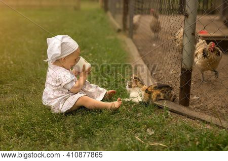 A Little Barefoot Girl Sits On The Grass In The Village And Drinks Milk From A Cup. The Cat Greedily