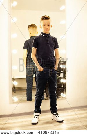 10-year-old Boy In A Hairdresser After A Fashionable Haircut In Front Of A Mirror. A Small Child In