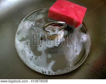 Cleaning And Washing Dishes. Glass Cover For  Saucepan With Red Sponge. Hand Dishwashing. Сoncept Of