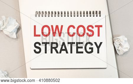 The Word Low Cost Strategy Is Written In A Notebook That Sits On A Gray Desktop Along With A Laptop.