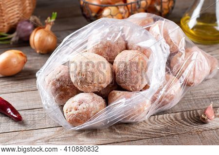 Semi-finished Products, Frozen Meatballs, Meat Patties In Plastic Bag On A Wooden Table