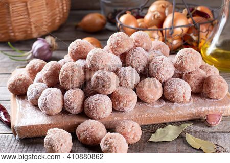 Frozen Meatballs On A Cutting Board On A Wooden Table