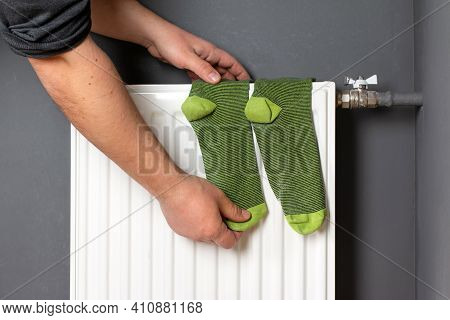 Man's Hand Hold Socks That Dry On Radiator. Domestic Heating Radiator.