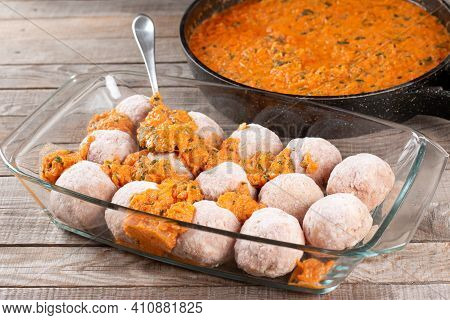 Frozen Raw Meatballs From Beef And Pork With Carrots And Rice In Sauce On A Wooden Table