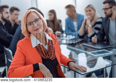 Businesswoman with colleagues sitting in a modern board room