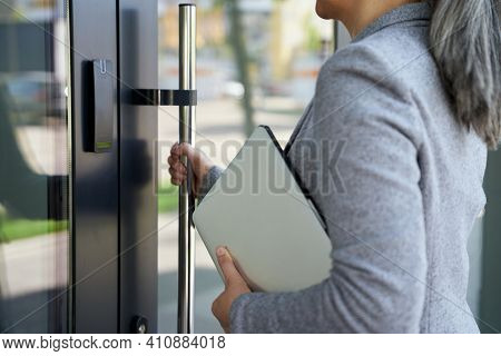 Cropped Short Of A Business Woman Holding Laptop And Opening The Main Door Of Office Building