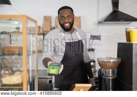 Cheerful And Friendly Multiracial Waiter, African Cafe Manager, Bakery Staff Is Holding Pos Payment