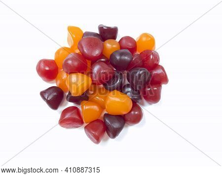 Close-up Texture Of Red, Orange And Purple Multivitamin Gummies On White Background. Healthy Lifesty