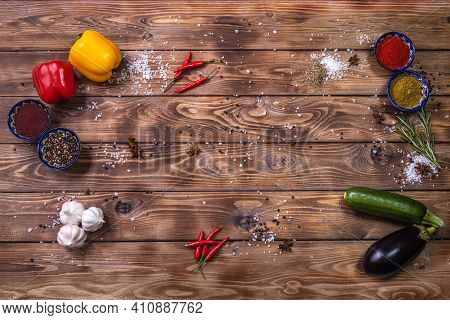 Flat Layout On A Brown Wooden Board Of Bell Pepper, Spices, Chili Pepper, Rosemary, Garlic, Eggplant
