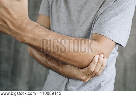 Close Up Of Man Suffering From Pain In Hand Or Elbow