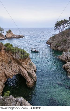 A Small Cove With Crystalline Waters And With A Small Cave, A Small Boat Is Sailing In It With Three