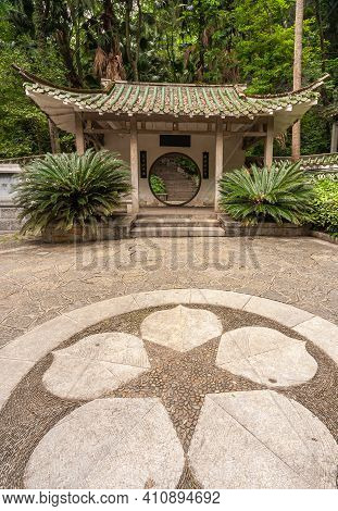 Guilin, China - May 11, 2010: 7 Star Park. Pavilion With Circular Doorway Set In White Wall With Man