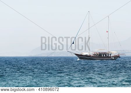 A Touristic Yacht With Tourists In Sea. Summer Beautiful Trip In The Sea In The Morning Sunlight.