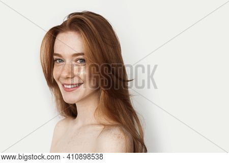 Red Haired Woman Is Smiling At Camera Wearing Hydrogel Eye Patches On A White Studio Wall
