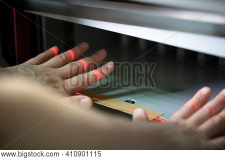 Faceless Woman Setting Up Paper Cutting Machine